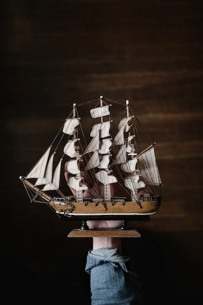 Picture of toy tall ship held by hand-symbol of grit