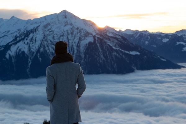 Image of man in jacket overlooking snow and mountains. Example of Good Grief